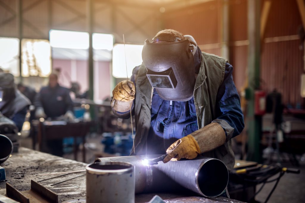 Profesional,Welder,In,Protective,Uniform,And,Mask,Welding,Metal,Pipe
